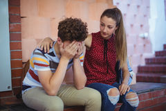 Schoolgirl sitting near staircase and consoling her sad friend Royalty Free Stock Images
