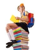 Schoolgirl sitting on pile of books. Stock Photography