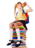 Schoolgirl sitting on pile of books. Stock Photo