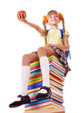 Schoolgirl sitting on pile of books. Stock Images