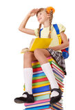 Schoolgirl sitting on pile of books. Stock Image