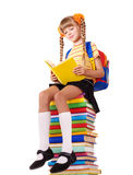 Schoolgirl sitting on pile of books. Stock Photography