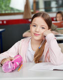 Schoolgirl Sitting With Pouch At Desk In Classroom Stock Photos