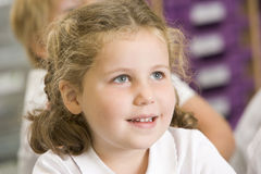 Schoolgirl sitting in primary class Stock Photography