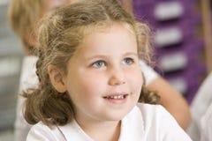 Schoolgirl sitting in primary class stock photography