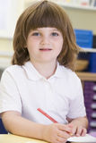 A schoolgirl sitting in a primary class Stock Photography