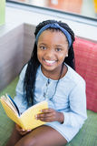 Schoolgirl sitting on sofa and reading book Royalty Free Stock Photo