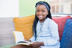 Schoolgirl sitting on sofa and reading book Stock Image