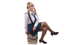 Schoolgirl is sitting on the stack of book. Royalty Free Stock Photography