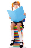 Schoolgirl sitting on stack of books. Royalty Free Stock Image