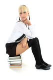 Schoolgirl sitting on stacked books Stock Photo