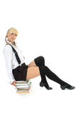 schoolgirl sitting on stacked books Stock Photo
