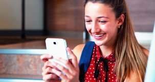Schoolgirl sitting on staircase and using mobile phone. At school stock video footage