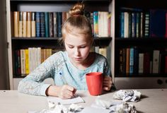 Schoolgirl sitting at table with pencil in hand. Royalty Free Stock Images