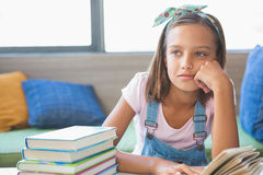 Schoolgirl sitting on table and reading book in library Stock Photos