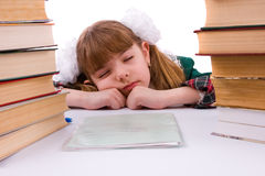Schoolgirl is sleeping near her homework. Royalty Free Stock Image