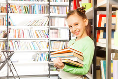 Schoolgirl smiles and holds books in library Stock Images