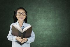 Schoolgirl smiling with book. Cute schoolgirl smiling at the camera while holding a textbook with copy space on the chalkboard Royalty Free Stock Photos