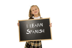 Schoolgirl smiling happy and cheerful holding and showing small blackboard with text I learn Spanish Royalty Free Stock Photography