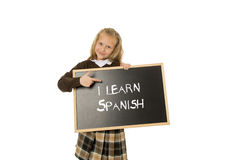 Schoolgirl smiling happy and cheerful holding and showing small blackboard with text I learn Spanish Royalty Free Stock Photos