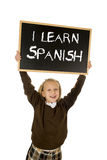 Schoolgirl smiling happy and cheerful holding and showing small blackboard with text I learn Spanish Royalty Free Stock Photo