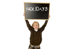 Schoolgirl smiling happy holding and showing blackboard with text holidays in end of school Stock Photos