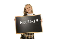 Schoolgirl smiling happy holding and showing blackboard with text holidays in end of school Royalty Free Stock Images