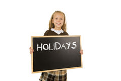 Schoolgirl smiling happy holding and showing blackboard with text holidays in end of school Stock Photography