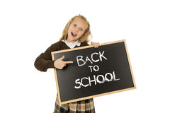 Schoolgirl smiling happy holding and showing small blackboard with text back to school Stock Image