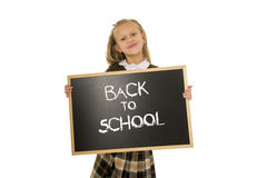 Schoolgirl smiling happy holding and showing small blackboard with text back to school Royalty Free Stock Images