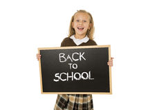 Schoolgirl smiling happy holding and showing small blackboard with text back to school Stock Images