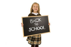 Schoolgirl smiling happy holding and showing small blackboard with text back to school Royalty Free Stock Photo