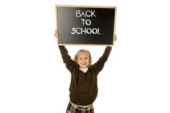Schoolgirl smiling happy holding and showing small blackboard with text back to school Stock Photography