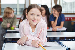 Schoolgirl Smiling While Leaning On Desk. Portrait of little schoolgirl smiling while leaning on desk with classmates in background Stock Photo
