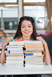 Schoolgirl Smiling With Stacked Books At Desk Stock Photos