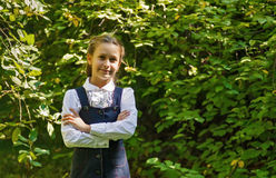 Schoolgirl smiling in white clothes. Schoolgirl teenager smiling in sunny green park Royalty Free Stock Photos