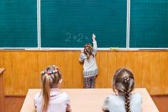 Schoolgirl solves an example of math Stock Photo