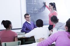 Schoolgirl solves task near blackboard in classroom mathematics Royalty Free Stock Photos