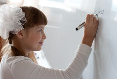 Schoolgirl is solving equation Stock Photos