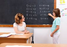 Schoolgirl solving math equations at chalkboard Royalty Free Stock Image