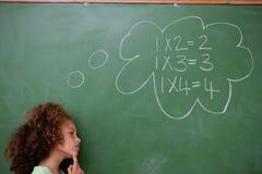Schoolgirl som är tänkande om algebra arkivfoto