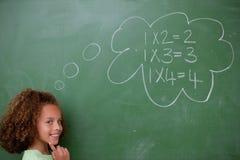 Schoolgirl som är tänkande om matematik arkivbild