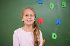 Schoolgirl som framme poserar av en blackboard Fotografering för Bildbyråer