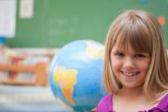 Schoolgirl som framme poserar av ett jordklot Arkivfoton