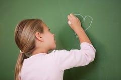 Schoolgirl som tecknar en hjärta Arkivfoto