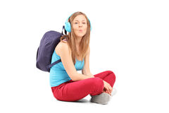 A schoolgirl with speakerphones sitting on a floor and giving ki Royalty Free Stock Photos