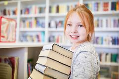 Schoolgirl with a stack of books to borrow. Smiling student with stack of books to borrow in the library of the school royalty free stock image