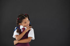 Schoolgirl standing against blackboard in classroom royalty free stock photo