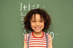 Schoolgirl standing against green board in a classroom at school. Front view of a cute mixed-race schoolgirl standing against green board in a classroom at royalty free stock photos