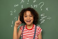 Schoolgirl standing against green board in a classroom at school. Front view of a mixed-race schoolgirl looking at the camera and raising her finger while stock images